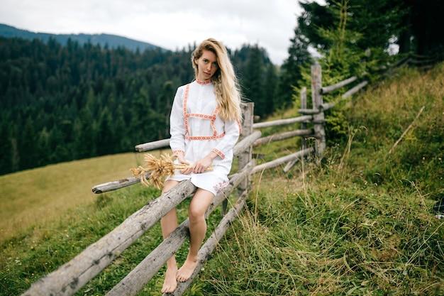Młoda atrakcyjna blondynka w białej sukni z ornamentem siedzi na drewnianym płocie z bukietem kłosków nad malowniczym krajobrazem wsi