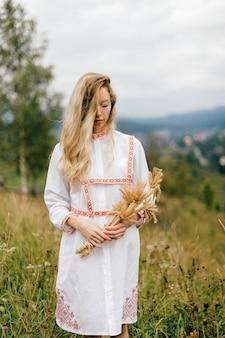 Młoda atrakcyjna blondynka w białej sukni z ornamentem z bukietem kłosków nad malowniczym krajobrazem wsi