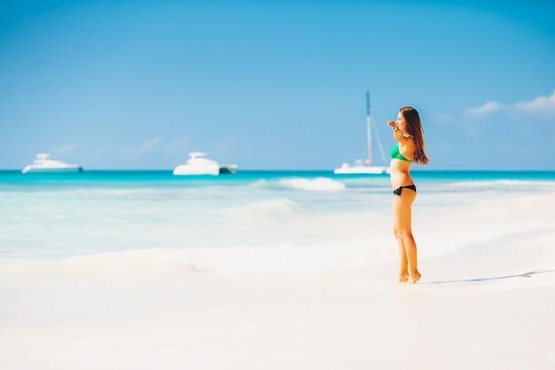 Młoda atrakcyjna blondynka w bikini na tropikalnej plaży