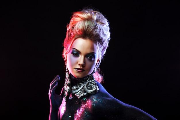 Młoda atrakcyjna blondynka w jasnym makijażu artystycznym, wysokich włosach, malowaniu ciała. dłoń na twarzy