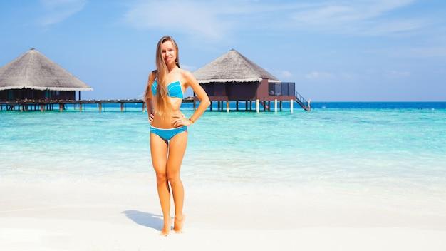 Młoda atrakcyjna blondynka z doskonałym sportowym ciałem w bikini na tropikalnej plaży latem w ośrodku