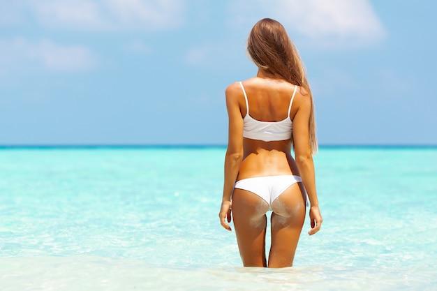 Młoda atrakcyjna blondynka z doskonałym sportowym ciałem w bikini na tropikalnej plaży latem