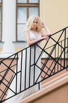 Młoda atrakcyjna blondynki panna młoda z kędzierzawym włosy odprowadzeniem w parku i ono uśmiecha się