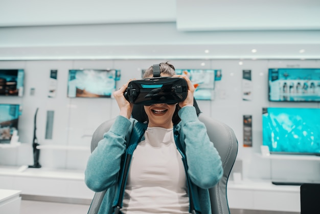 Młoda atrakcyjna brunetka kaukaska wypróbowuje technologię wirtualnej rzeczywistości i siedzi na krześle. wnętrze sklepu technicznego.