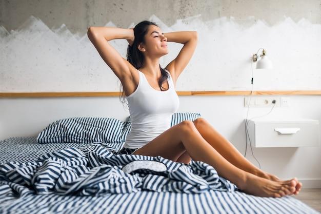 Młoda atrakcyjna brunetka kobieta siedzi na łóżku w piżamie i masce do spania, uśmiecha się w sypialni, szczęśliwe emocje, leniwy rano, budzi się, senny, seksowny, chude nogi