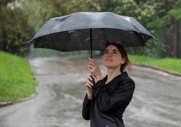 Młoda atrakcyjna brunetka łapie dłonią krople wody podczas deszczu