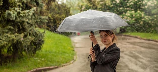 Młoda atrakcyjna brunetka łapie ręką krople wody podczas deszczu.