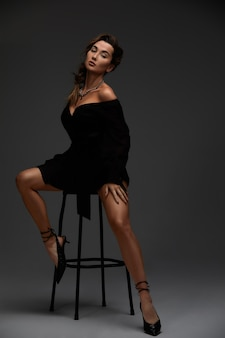 Młoda atrakcyjna brunetka sexy kobieta siedzi na krześle w erotycznej czarnej sukience koktajlowej