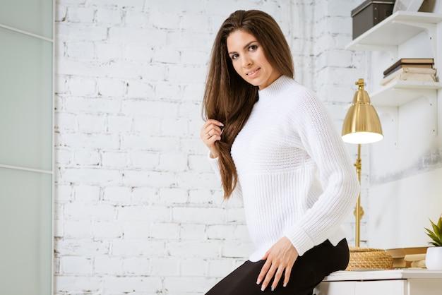 Młoda atrakcyjna brunetka w białym swetrze i czarnej spódnicy opiera się o krawędź stołu w ...