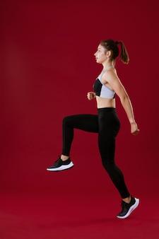 Młoda atrakcyjna brunetka w czarnych sportowych ubraniach skacze robi fitness portret na całej długości...