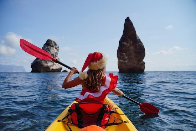 Młoda atrakcyjna brunetka w czerwonym stroju kąpielowym i santa hat pływa na kajaku wokół bazaltowych skał
