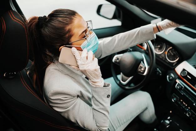 Młoda atrakcyjna brunetka z maską na twarz w gumowych rękawiczkach siedzi w swoim samochodzie i ma telefon podczas wybuchu choroby.