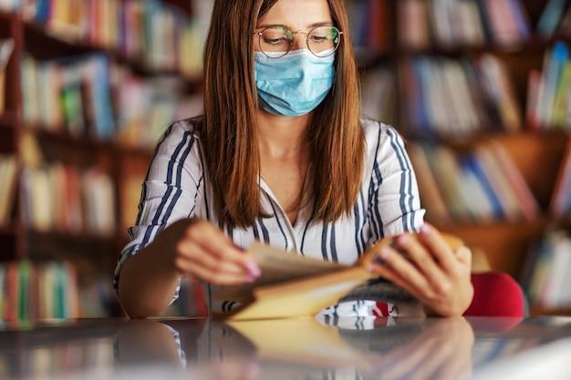 Młoda atrakcyjna brunetka z maską na twarzy siedząca w bibliotece i czytająca książkę.