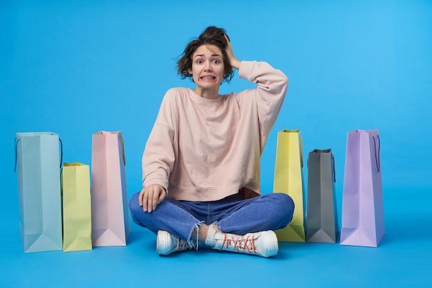 Młoda atrakcyjna ciemnowłosa kobieta z krótką fryzurą z dużą ilością toreb na zakupy