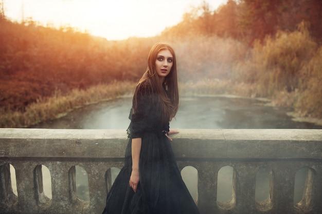 Młoda atrakcyjna czarownica chodząca po moście w ciężkim czarnym dymie.
