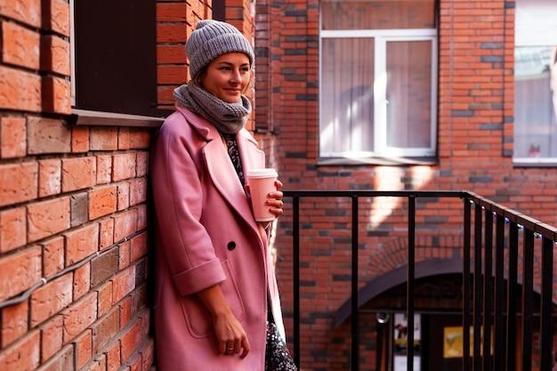 Młoda atrakcyjna dama w niebieskim kapeluszu dziewiarskim i różowym płaszczu trzymaj kawę na wynos. uśmiechnięta piękna hipster szczęśliwa kobieta na ulicy miasta, noszenie stylowych ubrań. jesienny trend, miejski styl stydent.
