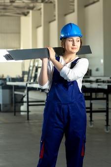 Młoda atrakcyjna dama w zdystansowanym widoku z przodu w niebieskim garniturze budowlanym i hełmie, trzymająca ciężki metaliczny detal podczas budowy architektury budynków w ciągu dnia