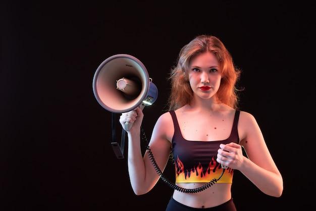 Młoda atrakcyjna dama z przodu w koszuli ognia i czarnych spodniach z megafonem na czarnym tle głośno krzyczy