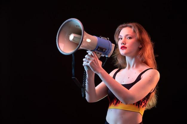 Młoda atrakcyjna dama z przodu w koszuli ognia i czarnych spodniach z megafonem na czarnym tle głośno