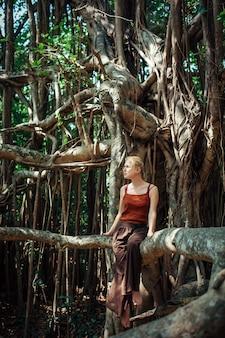 Młoda atrakcyjna dziewczyna cieszy się spokój na banyan drzewie w pogodnym letnim dniu