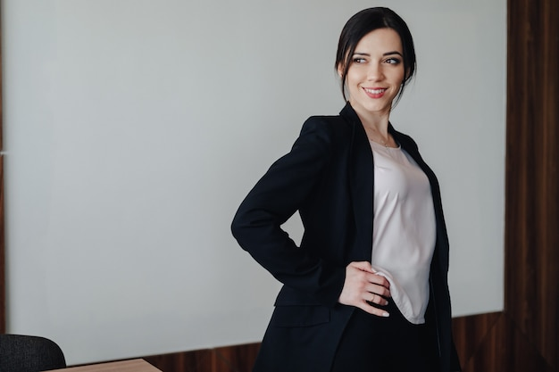 Młoda atrakcyjna dziewczyna emocjonalna w ubrania w stylu biznesowym na zwykłej białej powierzchni w biurze lub na widowni