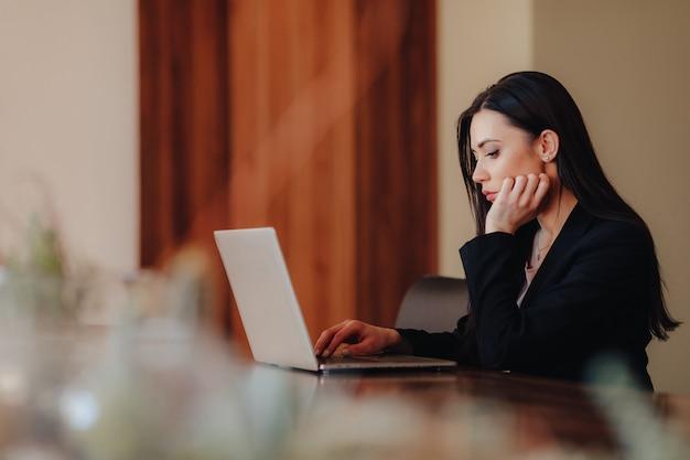Młoda atrakcyjna dziewczyna emocjonalne w ubrania w stylu biznesowym, siedząc przy biurku na laptopie i telefon w biurze lub audytorium