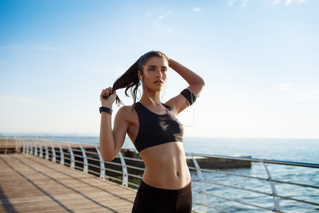 Młoda atrakcyjna dziewczyna fitness działa nad morzem