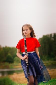 Młoda atrakcyjna dziewczyna gra na klarnecie, heban w jesiennym parku