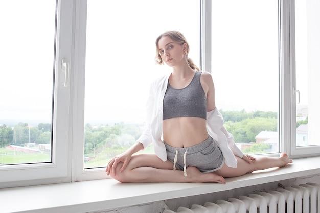 Młoda atrakcyjna dziewczyna o atletycznym ciele w sportowej odzieży, ćwiczy jogę, robi szpagat, ćwiczenia rozciągające na parapecie, ćwiczenia w pomieszczeniu