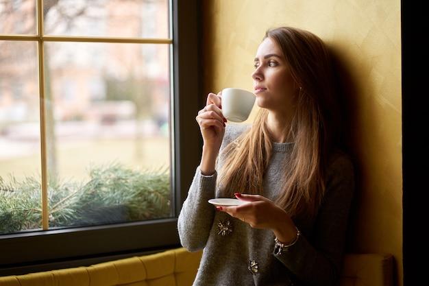 Młoda atrakcyjna dziewczyna pije kawę lub herbatę w kawiarni i patrząc przez okno.