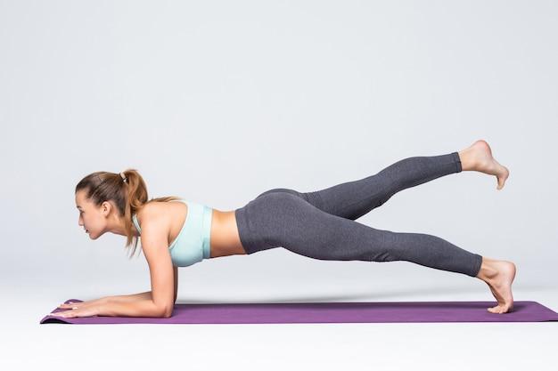 Młoda atrakcyjna dziewczyna praktykuje jogę na białym tle. pojęcie zdrowego życia i naturalnej równowagi między ciałem a rozwojem umysłowym. pełna długość