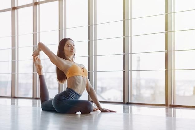 Młoda atrakcyjna dziewczyna robi ćwiczeń fitness z jogi na podłodze