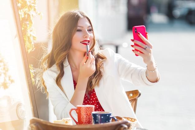 Młoda atrakcyjna dziewczyna robi selfie na telefonie komórkowym. piękny kobiety zakończenie w górę portreta outdoors. ładna dama trzyma telefon komórkowy.