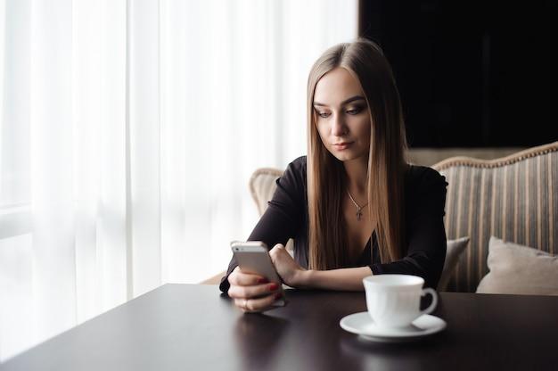 Młoda atrakcyjna dziewczyna siedzi samotnie w pobliżu dużego okna w kawiarni w czasie wolnym