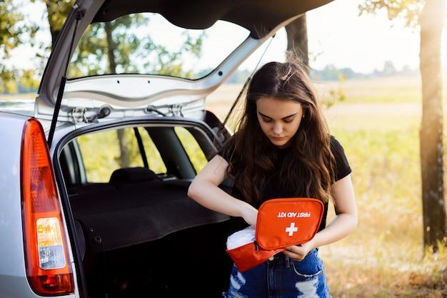 Młoda atrakcyjna dziewczyna stoi w pobliżu samochodu z otwartymi tylnymi drzwiami i włączonymi światłami awaryjnymi, próbuje znaleźć coś w apteczce