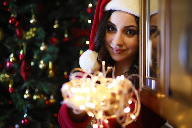 Młoda atrakcyjna dziewczyna ubrana w ciepłą piżamę i narzutę w pobliżu drzewa noworocznego. świąteczna atmosfera.