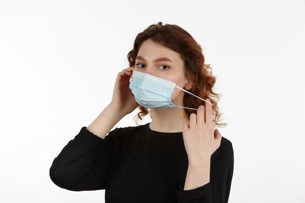 Młoda atrakcyjna dziewczyna w czarnych ubraniach nosi medyczną maskę ochronną.