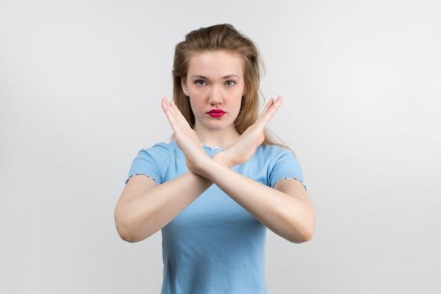 Młoda atrakcyjna dziewczyna w niebieską koszulę i piękne włosy pokazując znak stopu