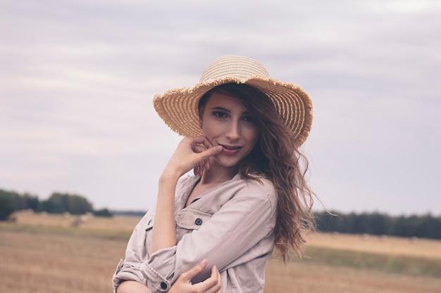 Młoda atrakcyjna dziewczyna w słomkowym kapeluszu w polu