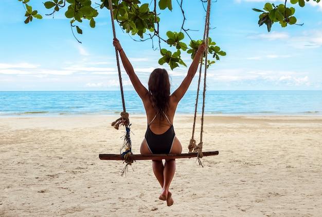 Młoda atrakcyjna dziewczyna w stroju kąpielowym siedzi na huśtawce na piaszczystej plaży nad oceanem i cieszy się widokiem. koncepcja wakacji.