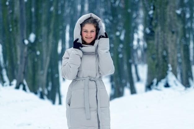 Młoda atrakcyjna dziewczyna w zimowe ubrania w zimie w lesie na tle drzew i śniegu