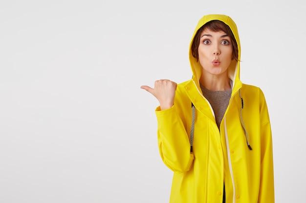 Młoda atrakcyjna dziewczyna w żółtym płaszczu przeciwdeszczowym z zaskoczonym wyrazem twarzy chce zwrócić twoją uwagę na przestrzeń kopii po lewej, wskazując palcem na białą ścianę.