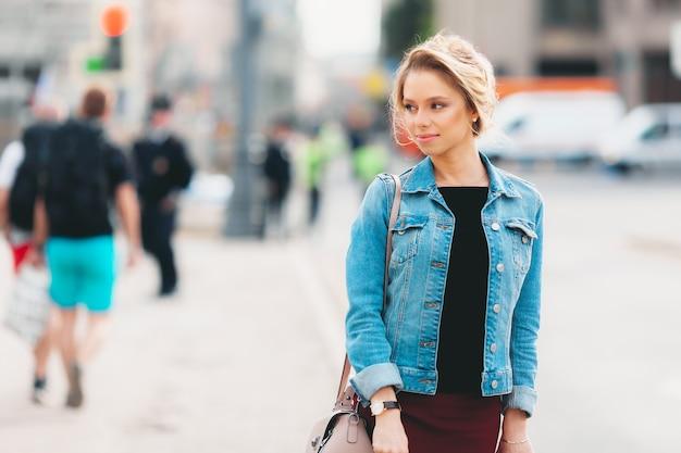Młoda atrakcyjna dziewczyna z makijażem w dżinsach na ulicy w lecie