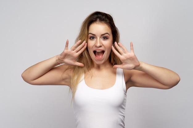 Młoda atrakcyjna dziewczyna z okrzykami pozytywnego i emocjonalnego krzyku szeroko otworzyła usta i zacisnęła dłonie na rogu patrząc w kamerę. zniżki, gorące oferty, świeże wiadomości