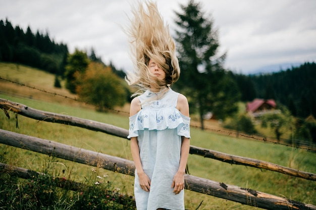 Młoda atrakcyjna elegancka blondynka w niebieskiej sukience z rozwianymi włosami pozowanie w pobliżu ogrodzenia na wsi