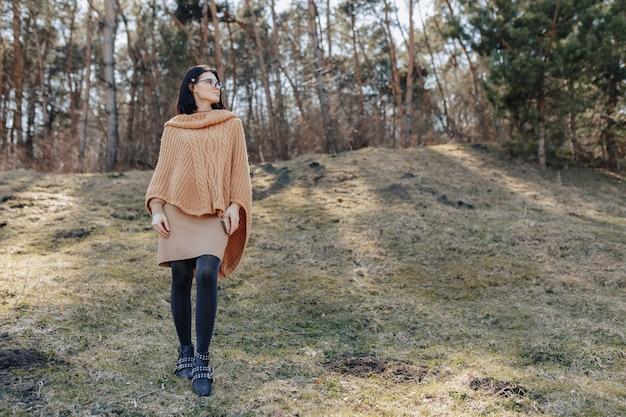 Młoda atrakcyjna elegancka dziewczyna na naturze na las ścianie z telefonem w słonecznym dniu. wakacje na świeżym powietrzu i zależność od technologii.