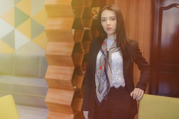 Młoda atrakcyjna emocjonalna dziewczyna w biznesowym stylu przy krzesłem w nowożytnym biurze lub widowni