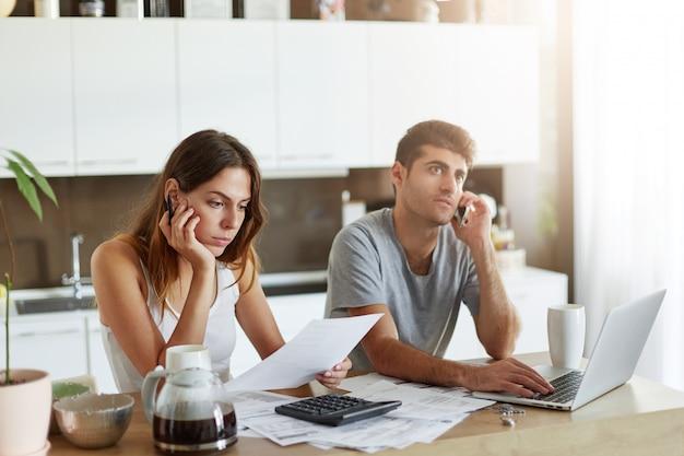 Młoda atrakcyjna europejka siedzi przy kuchennym stole obok męża, uważnie czytając umowę, obliczając dane za pomocą kalkulatora. przystojny mężczyzna podejmowania rozmów biznesowych przez telefon komórkowy