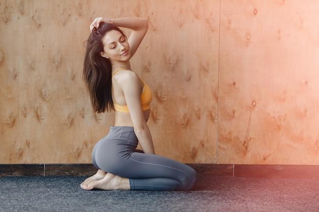Młoda atrakcyjna fitness dziewczyna siedzi na podłodze w pobliżu
