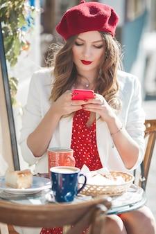 Młoda atrakcyjna francuska dziewczyna robi selfie na telefonie komórkowym. ładna dama trzyma telefon komórkowy.